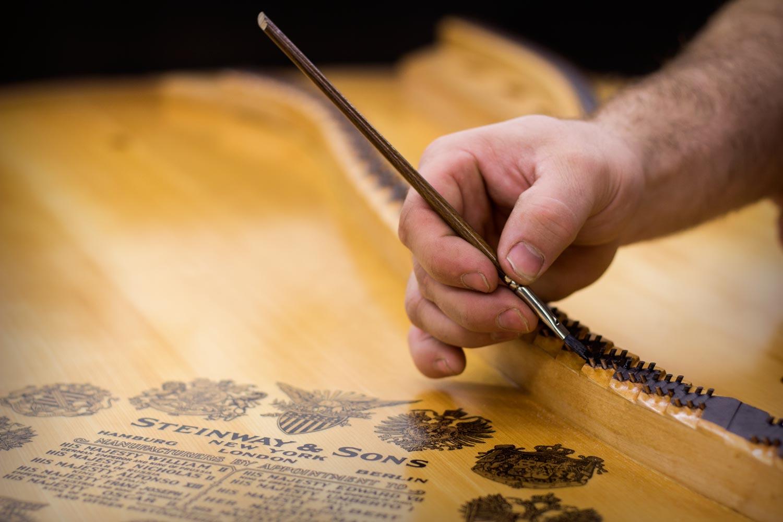 Expert Piano Rebuilding & Piano Restoration - Painting Soundboard Bridges.